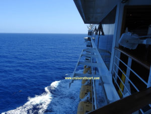 Port side view of ship at sea with water breaking to the left side - Solo Cruising
