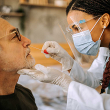 Healthcare worker swabbing inside man's nose